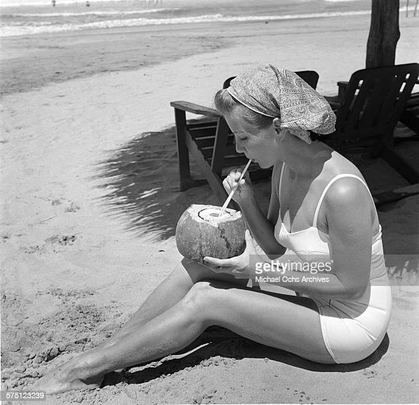 A woman sips a drink from a coconut on the sandy beach in Acapulco Mexico