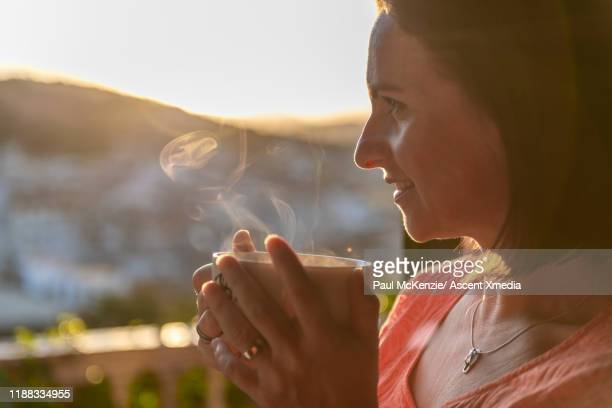 woman sips hot beverage and watches sun rise over village - hot spanish women stock pictures, royalty-free photos & images