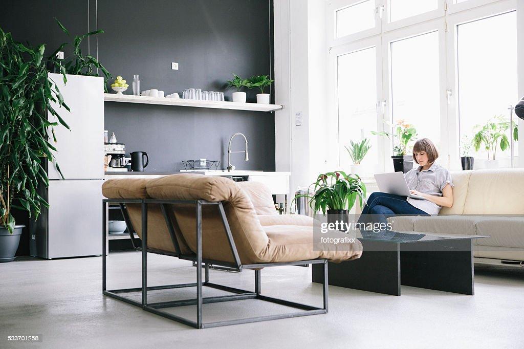 Donna sedersi sul divano nel comfort e il lavoro al computer portatile : Foto stock