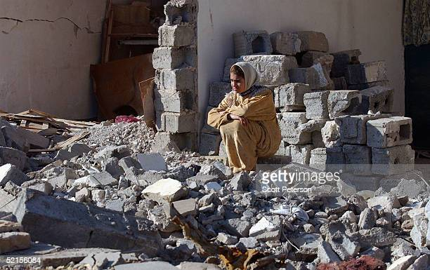 A woman sits alone among the ruins of her house on February 7 as residents return to rebuild their lives after a full scale US invasion to crush...