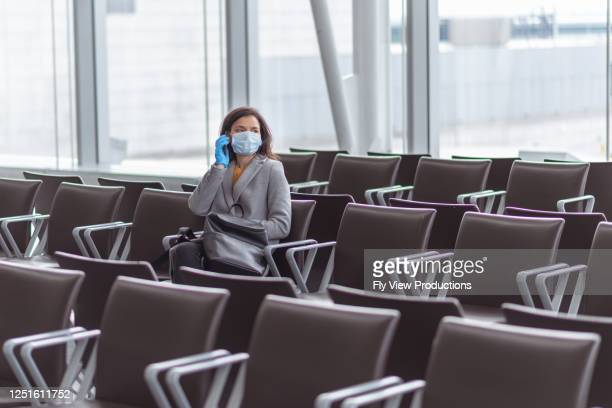 a woman sits alone at airport during pandemic - travel ban stock pictures, royalty-free photos & images