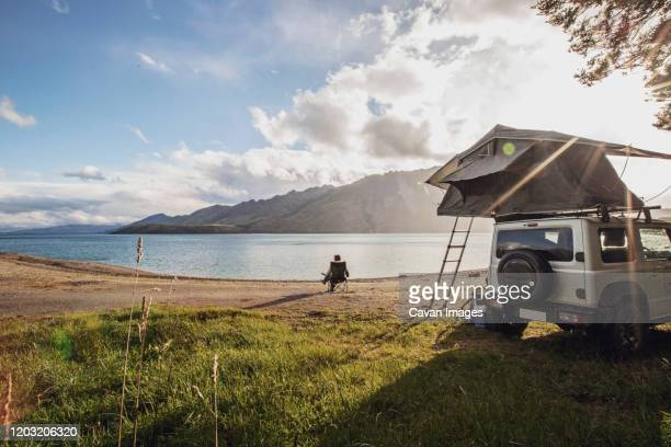 a woman sits along a lake next to a suv with a tent in new zealand - ニュージーランド南島 ストックフォトと画像