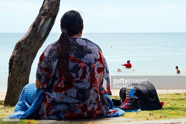 A woman sits along the beach looking out at sea in Noumea on December 1 2014 Obesity and diabetes are affecting citizens throughout the South Pacific...