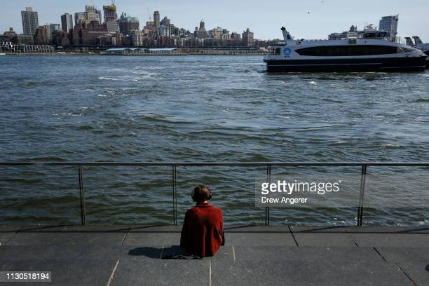 A woman sits along the East River near the South Street Seaport March 14 2019 in New York City Mayor Bill de Blasio has unveiled a $10 billion plan...