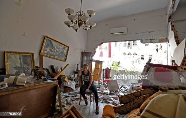 Woman sits amidst the rubble in her damaged house in the Lebanese capital Beirut on August 6 two days after a massive explosion shook the Lebanese...
