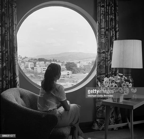 A woman sits and looks out a circular window in an apartment in Caracas Venezuela
