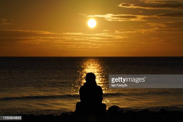 A woman sits and watches the sunrise at Saltburn beach on the morning of the summer solstice on June 20 2020 in SaltburnbytheSea England The summer...