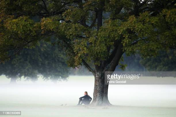 A woman sits and watches the sunrise in Hagley Park opposite the Al Noor mosque March 17 2019 in Christchurch New Zealand 49 people are confirmed...