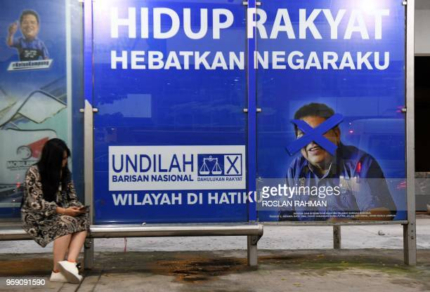 A woman sits at a bus stop with a vandalised campaign poster for Barisan Nasional candidate for Putrajaya Tengku Adnan Tengku Mansor in Kuala Lumpur...