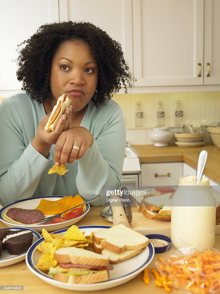 Woman Sits at a Kitchen Table Eating a Lunch of Cheese and Salami Sandwiches and Crisps : Stock Photo