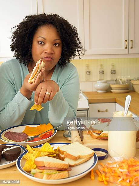 Woman Sits at a Kitchen Table Eating a Lunch of Cheese and Salami Sandwiches and Crisps
