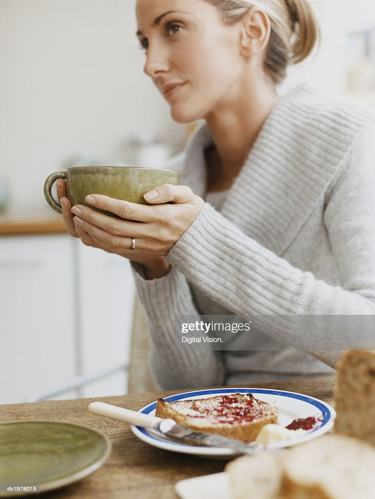 Woman Sits at a Table Holding a Cup, Plate With Toast on Table : Stock Photo