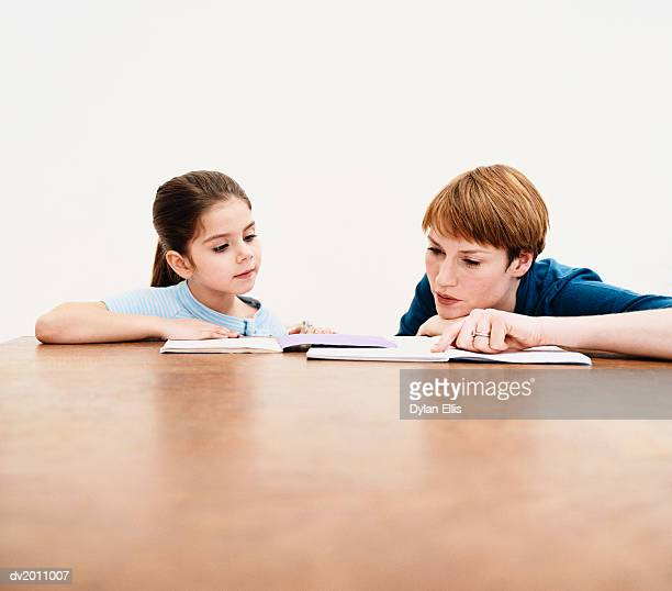 Woman Sits at a Table With Her Daughter, Helping Her With Her Homework