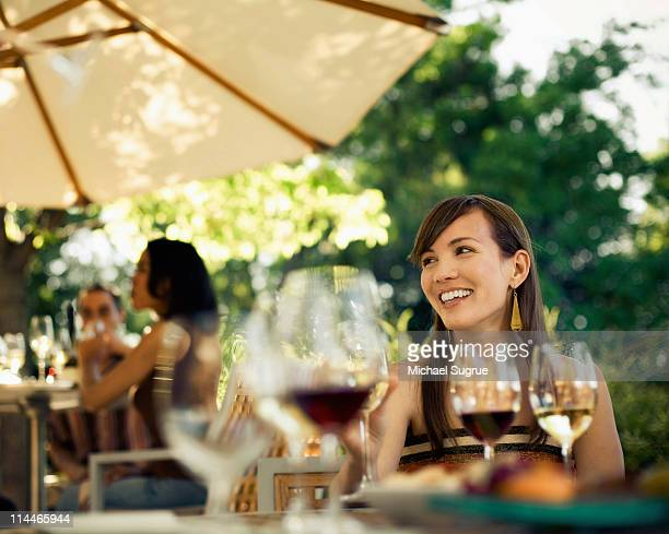 a woman sits at an outdoor table with friends. - healdsburg stock pictures, royalty-free photos & images
