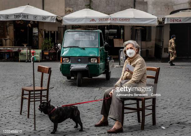 Woman sits at Campo dei Fiori Square while queuing at a local market on May 2, 2020 in Rome, Italy. Italy will remain on lockdown to stem the...