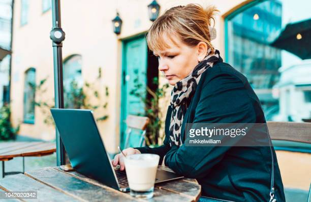 Woman sits at outdoor cafe using her laptop computer