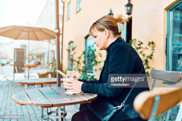 Woman sits at outdoor cafe using her smart phone