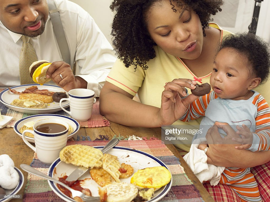 Woman Sits at the Breakfast Table With Her Husband, Feeding Her Toddler a Doughnut : Stock Photo