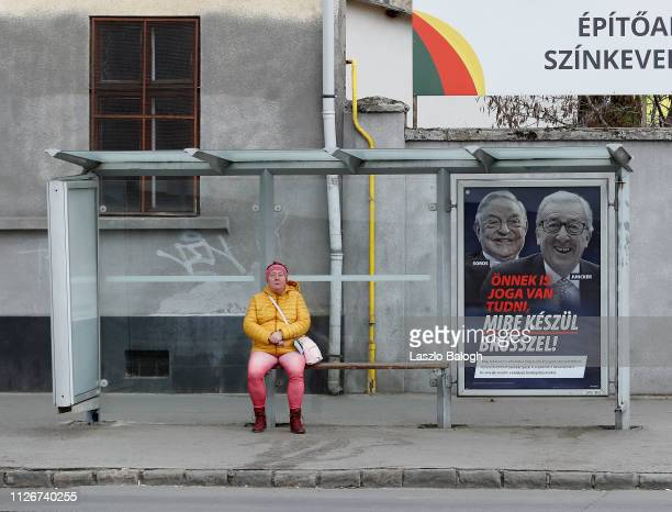 A woman sits at the bus stop next to a billboard with portraits of European Commission chief JeanClaude Juncker and Hungarianborn US billioner George...
