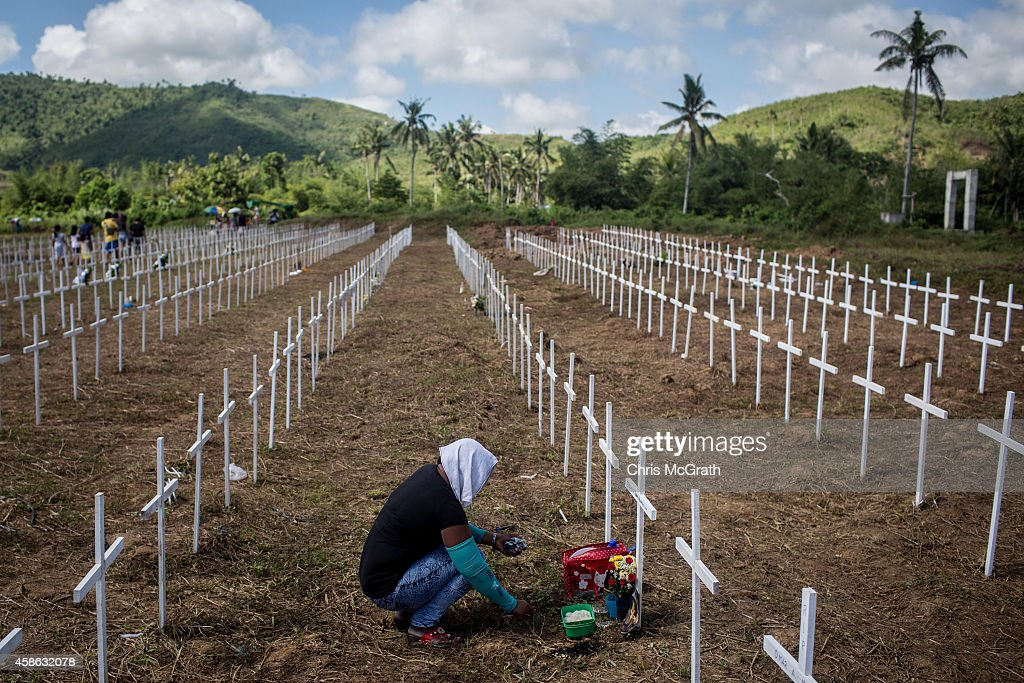 TACLOBAN, LEYTE, PHILIPPINES - NOVEMBER 08: A woman sits at the cross of a loved one at the mass grave on the grounds of the Holy Cross Memorial Garden on November 8, 2014 in Tacloban, Leyte, Philippines. Residents and typhoon survivors from across the central Philippines attended memorial services and visited mass graves honouring those who lost their lives one year ago when Typhoon Haiyan, the strongest typhoon ever to make landfall swept across the region, leaving more than 6000 dead and many more homeless.