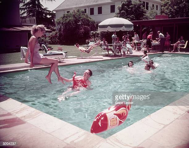 A woman sits at the edge of a diving board while others play with inflatable animals in a swimming pool during a pool party at the home of swimwear...
