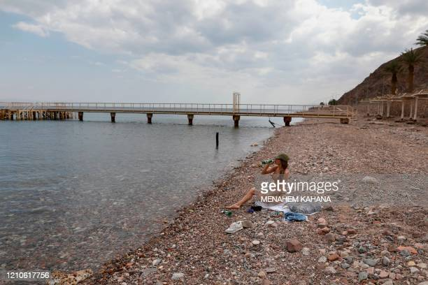 Woman sits at the empty Red Sea shore in the southern Israeli resort city of Eilat on April 17, 2020 amid the coronavirus COVID-19 pandemic. - Due to...