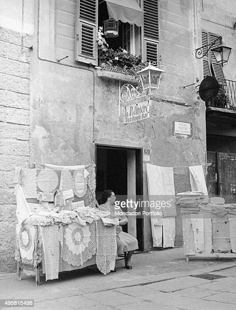 A woman sits at the entrance of the bartearoom La Polinière where she exposes laces and embroidery the sign of the bar is posed under a...
