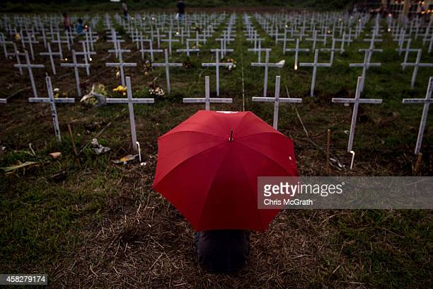 TACLOBAN LEYTE PHILIPPINES NOVEMBER 02 A woman sits at the grave of a loved one at a newly constructed mass grave for 3000 typhoon Haiyan victims on...