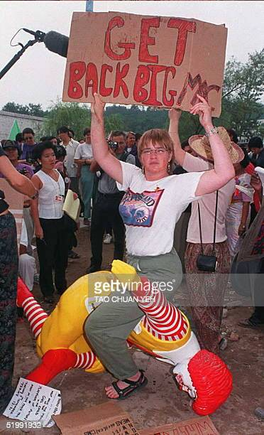 A woman sits atop the Ronald McDonald statue after some demonstrators destroyed the display for the restaurant's outlet at the Women's NGO Forum site...