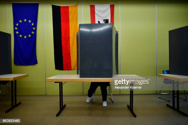 Woman sits behind voting booths as she fills in her election ballots at a polling station during German federal elections on September 24, 2017 in...