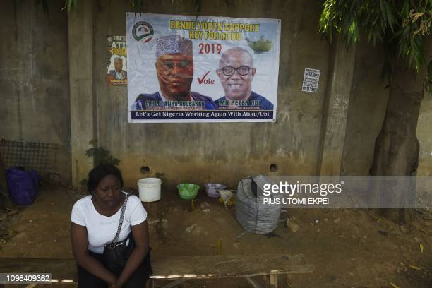 A woman sits beside a poster at the campaign headquarters of main opposition PDP party presidential candidate Atiku Abubakar and his running mate for...