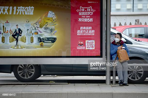 A woman sits beside a promotional billboard seen at a bus stop in Beijing on November 11 2015 Shoppers spent around 9 billion USD in the first 12...