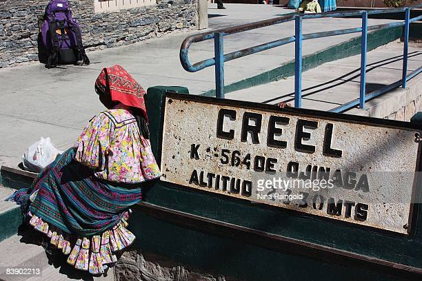 Woman sits beside a town sign in the farming and logging town of Creel on November 25, 2008 in Mexico. Creel is one of the main tourist attractions...