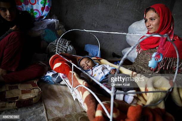 A woman sits beside her baby with her family in a temporary room in a refugee camp after crossing from Syria into Turkey in Suruc September 28 2014...