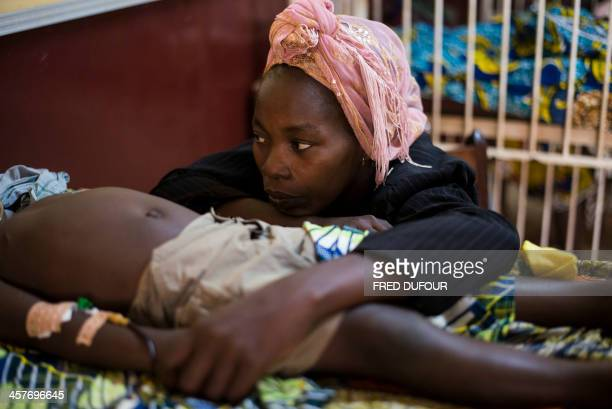 A woman sits beside her son sick with malaria at the pedriatic hospital in Bangui on December 18 2013 The Central African Republic's interim...
