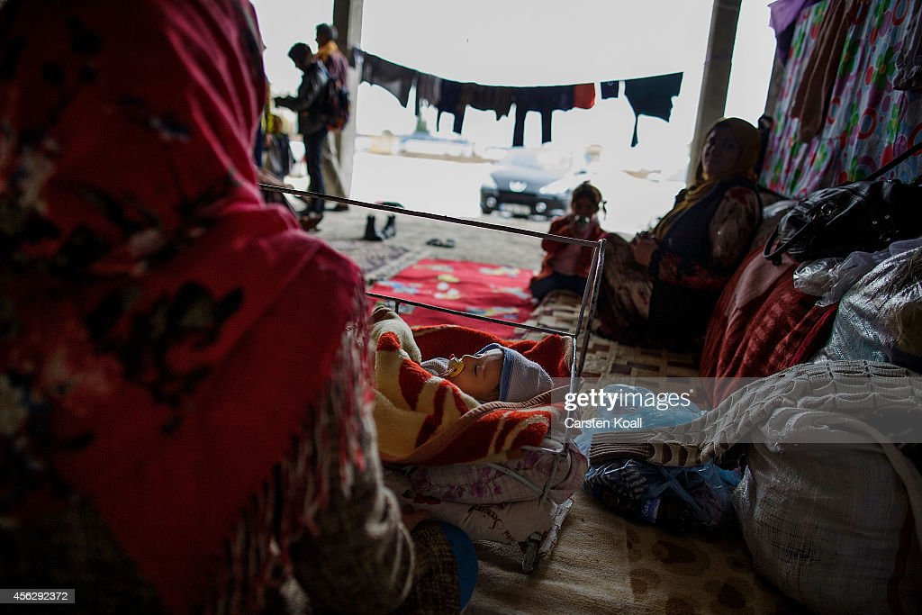 A woman sits beside the cradle of a baby with her family in a temporary room in a refugee camp after crossing from Syria into Turkey in Suruc September 28, 2014 south of Sanliurfa, Turkey. Islamic State (IS, also called ISIS and ISIL) fighters are reportedly advancing with heavy weaponry on the strategic Kurdish border town of Kobani (also called Ayn Al-Arab), which they have surrounded on three sides. Several hundred thousand refugees are reportedly in Kobani and aid agencies are bracing for a massive exodus into Turkey.