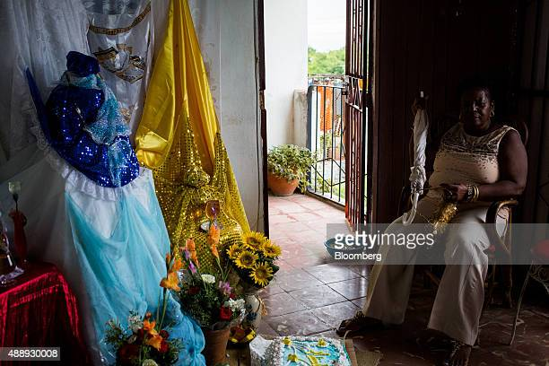 A woman sits by a shrine during a Santeria celebration at a home in Havana Cuba on Wednesday Sept 17 2015 Cubans often pray to Catholic saints that...