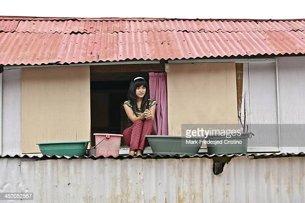 Woman sits by a window after rain from the southwest monsoon flooded towns in Angono, Rizal on August 9, 2012.