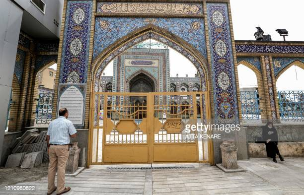 A woman sits by the fence as a man stands before the closed gate outside the Imamzadeh Saleh in the Iranian capital Tehran's Shemiran district on...