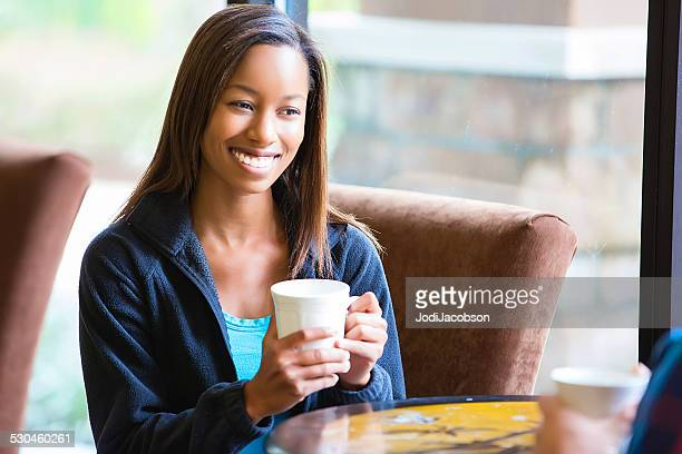 Woman sits by window with a cup of coffee