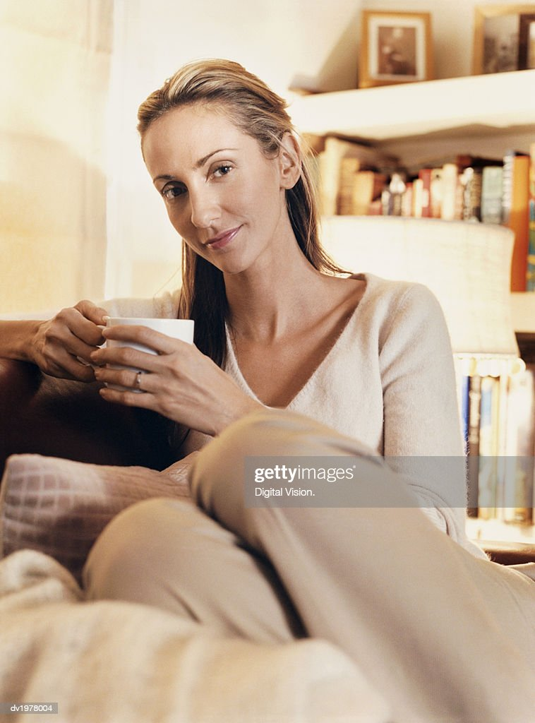 Woman Sits Comfortably in Armchair Holding a Cup : Stock Photo