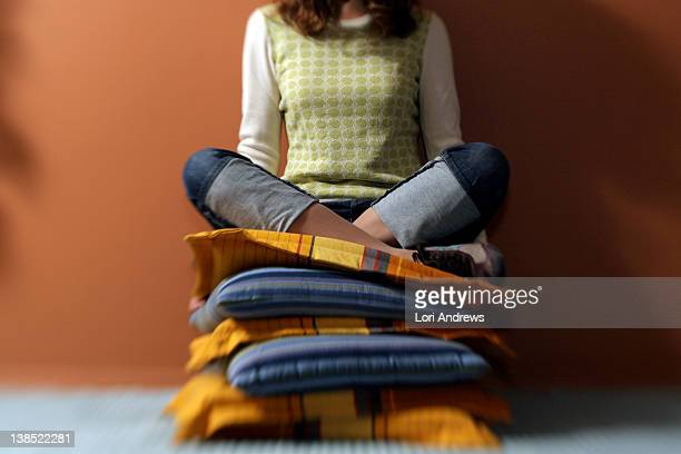 woman sits cross legged on stack of cushions - cushion stock pictures, royalty-free photos & images