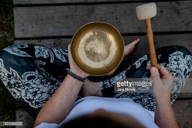 woman sits cross-legged and holds a singing bowl in her hands - top view - rin gong stock pictures, royalty-free photos & images
