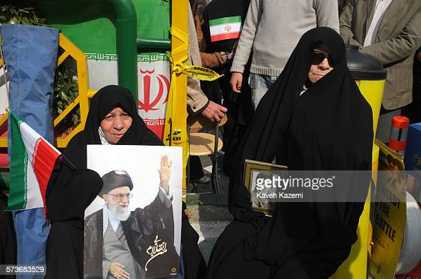A woman sits holding a framed photo of her martyred son while the other holds a poster with a photo of Iran's supreme leader Ayatollah Ali Khamenei...
