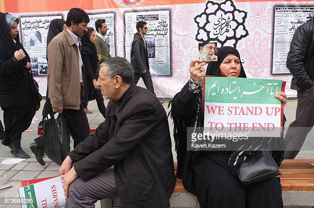 """Woman sits holding a photo of Iran's supreme leader Ayatollah Ali Khamenei and a banner reading """"We Stand Up To The End"""" during a march on Revolution..."""