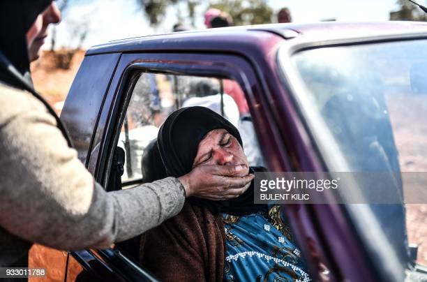 TOPSHOT A woman sits in a car as people arrive at a check point in the village of Anab ahead of crossing to the Turkishbacked Syrian rebels side on...