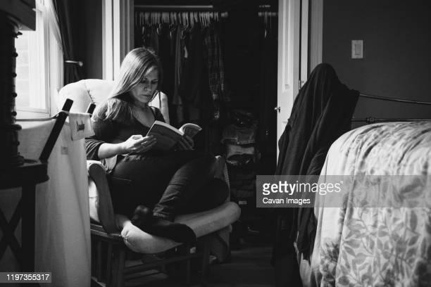 a woman sits in a chair reading a book. - schwarzweiß bild stock-fotos und bilder