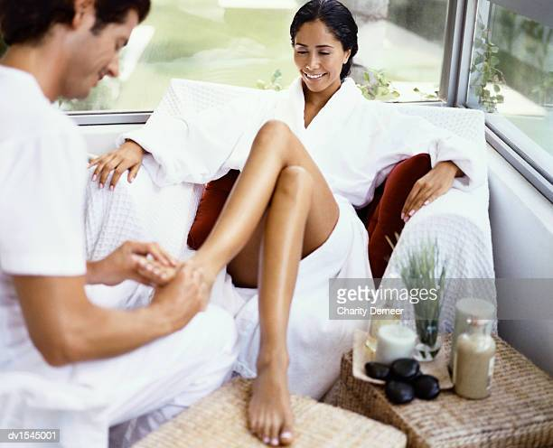 Woman Sits in a Dressing Gown Having Her Feet Massaged By a Physical Therapist