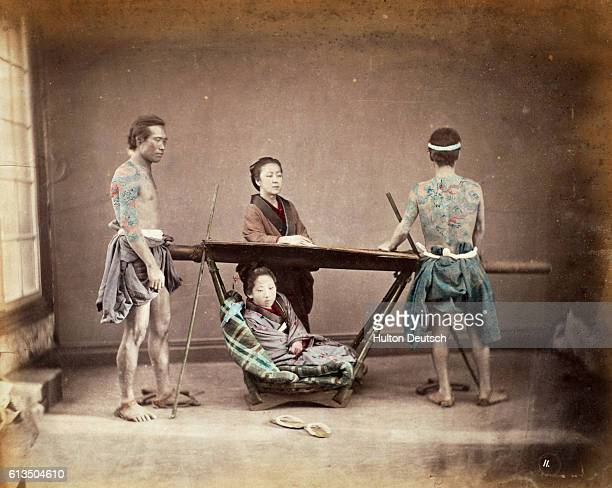 A woman sits in a sedan chair placed to rest by two tattoed bearers
