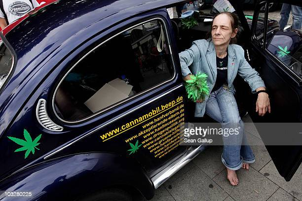 A woman sits in a VW Beetle decorated with painted marijuana plants prior to participating in the annual Hemp Parade or 'Hanfparade' in support of...